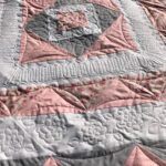 Pink and gray baby quilt with custom floral quilting